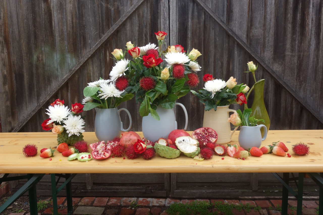 Table arrangements with roses dahlias and fruit