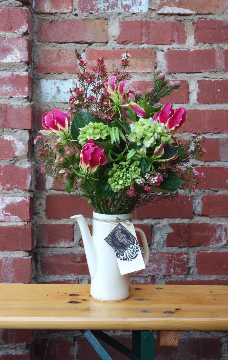 Gloriosa, waxflower, leucospermum & hydrangea arrangement